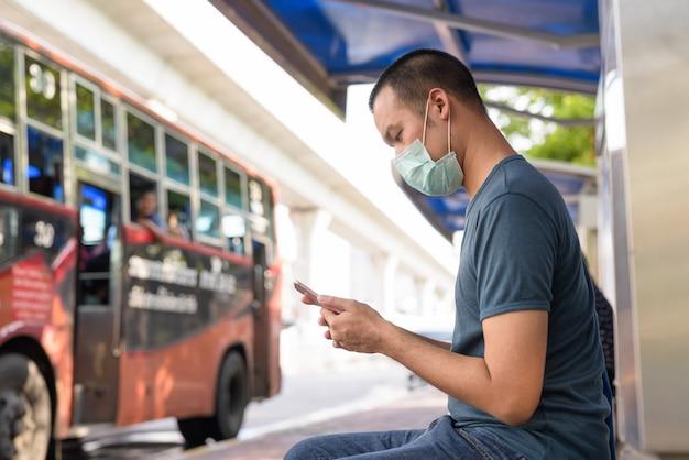 Vista de perfil de jovem asiático usando telefone com máscara para proteção contra surto de coronavírus no ponto de ônibus