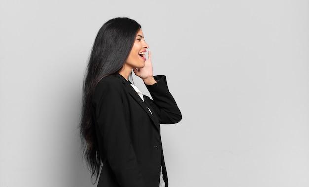 Vista de perfil de jovem empresária hispânica, parecendo feliz e animada, gritando e ligando para copiar o espaço ao lado