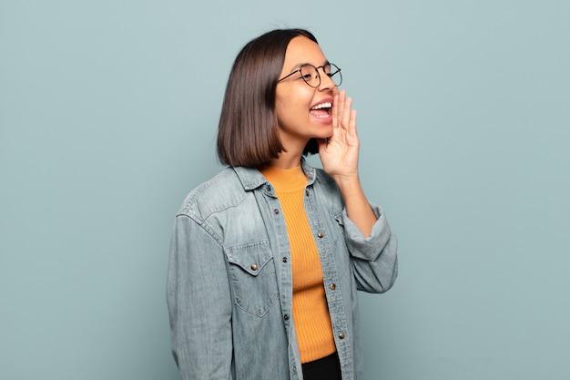 Vista de perfil de jovem hispânica, parecendo feliz e animada, gritando e chamando para copiar o espaço ao lado