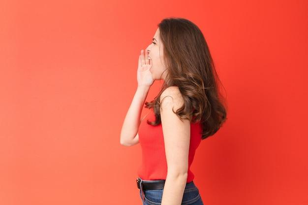 Vista de perfil de mulher bonita jovem, olhando feliz e animado, gritando e chamando para copiar o espaço do lado contra a parede vermelha