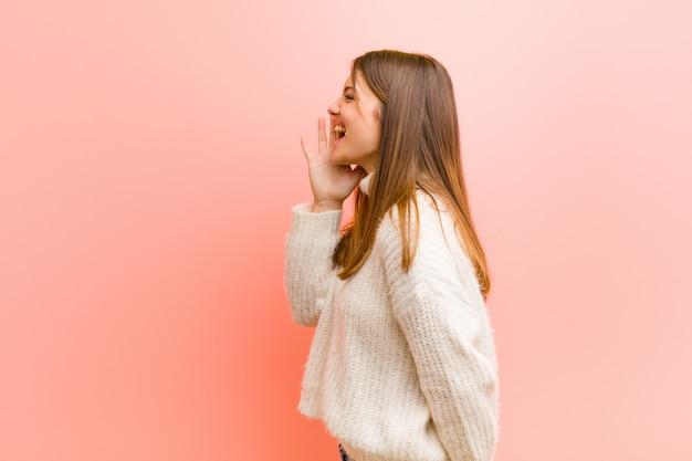 Vista de perfil de mulher bonita jovem, olhando feliz e animado, gritando e chamando para copiar o espaço do lado contra o fundo rosa