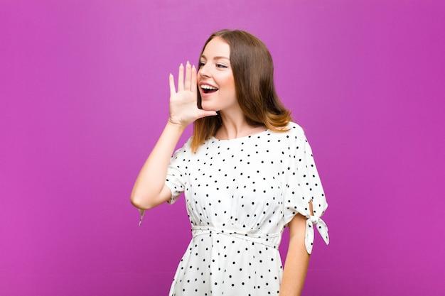 Vista de perfil de mulher cabeça vermelha, olhando feliz e animado, gritando e chamando para copiar o espaço do lado na parede roxa
