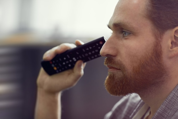 Vista de perfil de tv assistindo homem bonito