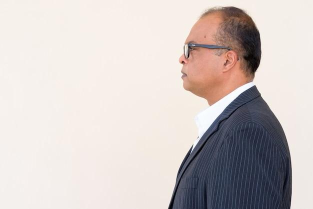 Vista de perfil de um empresário indiano contra uma parede simples ao ar livre