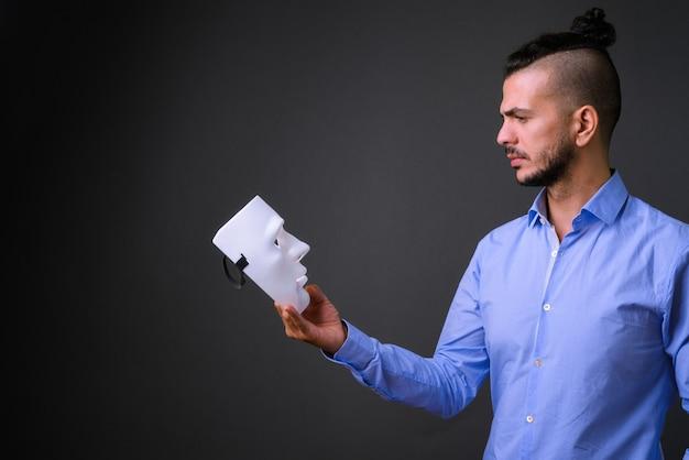 Vista de perfil de um empresário turco barbudo olhando para uma máscara branca