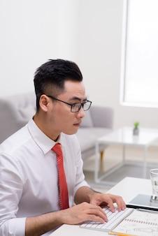 Vista de perfil de um jovem bonito fazendo alguns exercícios de meditação enquanto trabalhava no escritório