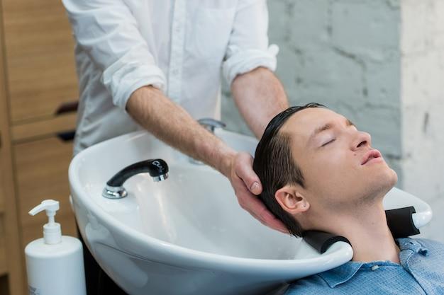Vista de perfil de um jovem se preparando para a lavagem do cabelo