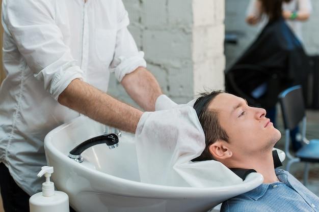 Vista de perfil de um jovem se preparando para o cabelo lavado