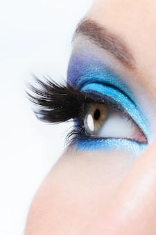 Vista de perfil de um olho feminino com maquiagem azul brilhante e longos cílios postiços pretos