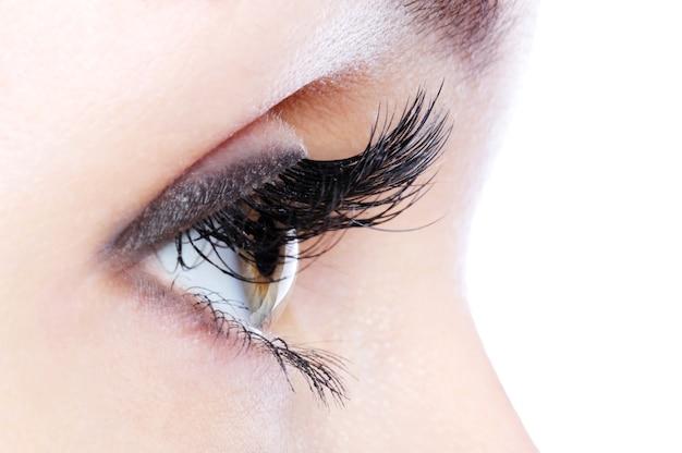 Vista de perfil de um olho humano com cílios postiços longos e curvados