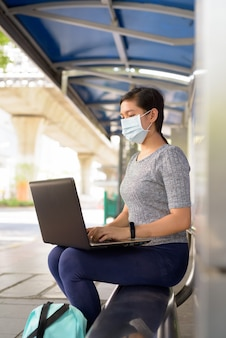 Vista de perfil de uma jovem asiática com máscara usando laptop enquanto está sentado no ponto de ônibus