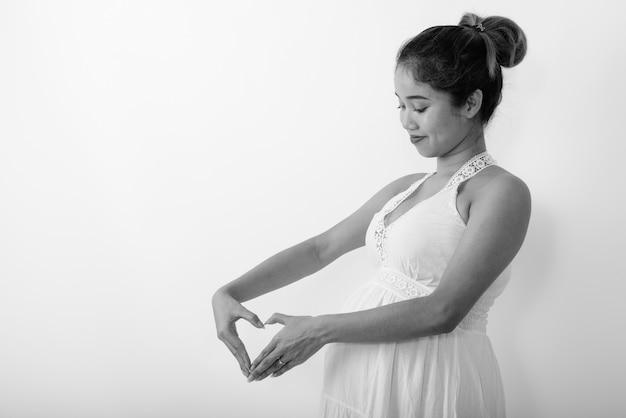 Vista de perfil de uma jovem asiática grávida fazendo sinal de coração com a mão ao lado de sua barriga contra uma parede branca