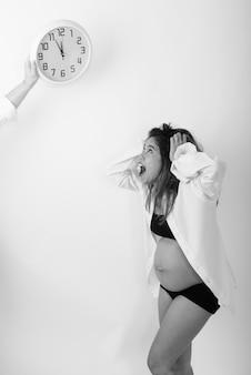 Vista de perfil de uma jovem grávida asiática parecendo chocada enquanto olha para o relógio de parede contra a parede branca