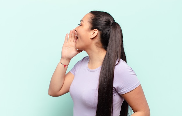 Vista de perfil de uma mulher latina, parecendo feliz e animada, gritando e chamando para copiar o espaço ao lado