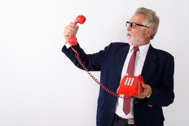 Vista de perfil do empresário barbudo sênior com raiva segurando e olhando para o telefone antigo em branco