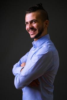 Vista de perfil do feliz empresário turco barbudo sorrindo com os braços cruzados