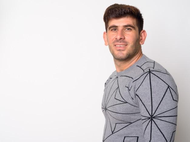 Vista de perfil do jovem persa feliz olhando para a câmera