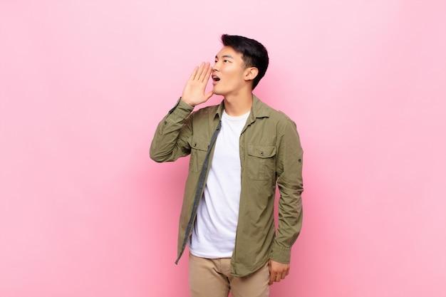 Vista de perfil jovem chinês, olhando feliz e animado, gritando e chamando para copiar o espaço do lado na parede de cor lisa