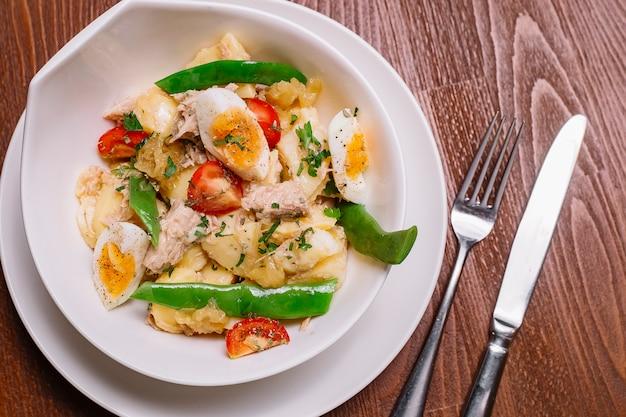 Vista de perto da tigela de salada de batata italiana com atum e tomate cereja