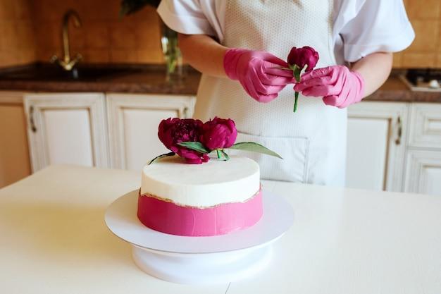 Vista de perto das mãos de uma mulher em luvas decorando um lindo bolo com peônias