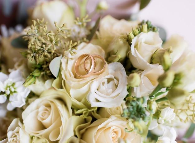 Vista de perto de duas alianças de ouro sobre o buquê de rosas