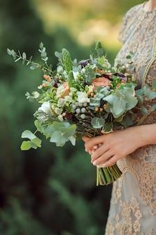 Vista de perto de um lindo buquê de casamento colorido na mão de uma noiva contra o bokeh verde do fundo da natureza