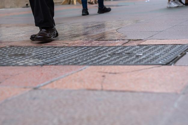 Vista de perto dos pés das pessoas andando na rua comercial.