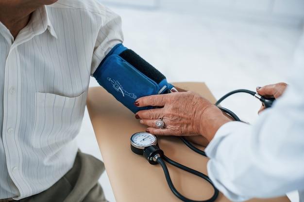 Vista de perto. médica usa tonômetro para medir a pressão arterial para homem sênior.