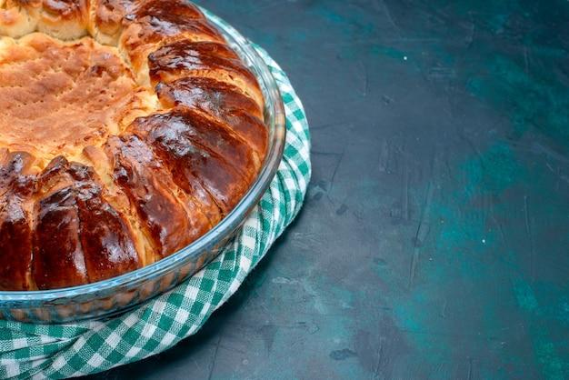 Vista de perto o delicioso bolo assado redondo formado doce dentro da panela de vidro sobre fundo azul claro.