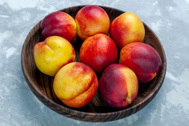 Vista de perto pêssegos frescos e frutas saborosas dentro de um prato marrom em uma mesa branca