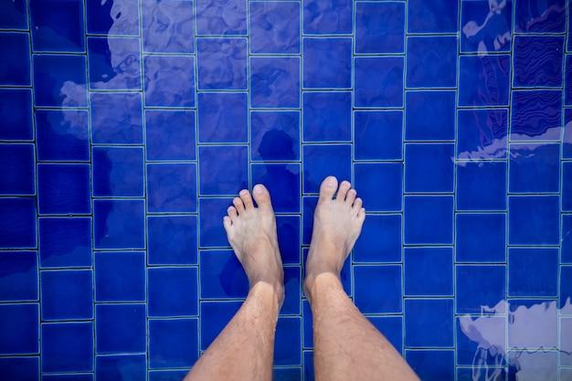 Vista de pés descalços masculinos em pé ao lado da piscina.
