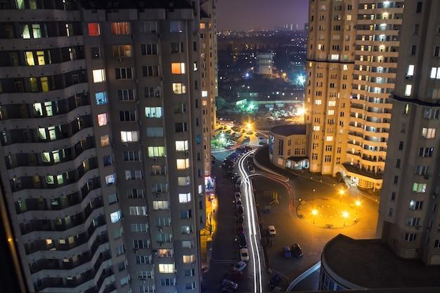 Vista de prédios altos com janelas à noite com iluminação e carros em movimento com luz desfocada
