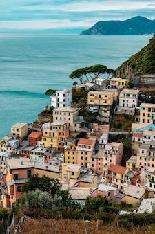 Vista de riomaggiore do topo da colina. antiga vila do parque nacional cinque terre, na ligúria, itália