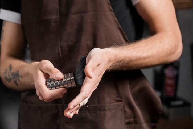 Vista de seção intermediária da mão de um barbeiro com pincel de barba