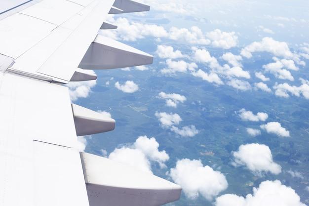 Vista de terra, nuvem e asa de avião da janela