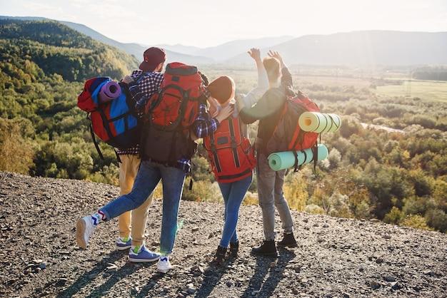 Vista de trás de quatro amigos hipster com mochila de viagem