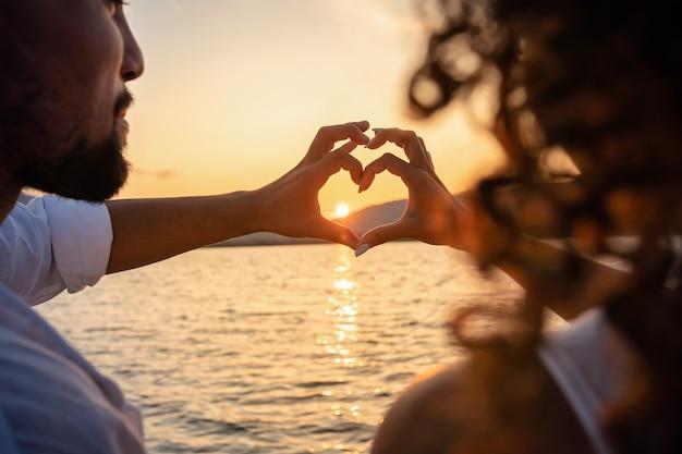 Vista de trás de um jovem casal lindo fazendo formato de coração com os dedos olhando para o pôr do sol atrás das montanhas.