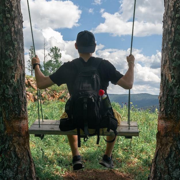 Vista de trás de um jovem em um boné em um balanço contra um fundo de nuvens.