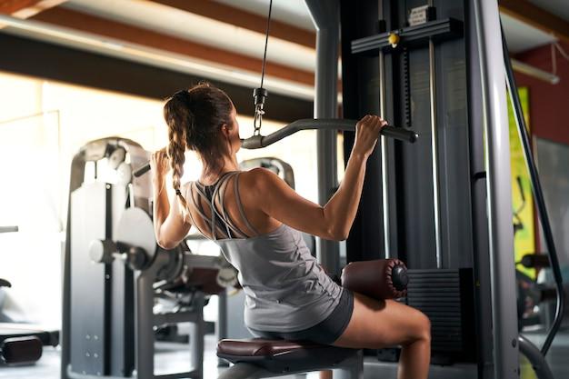 Vista de trás de uma jovem com shorts esportivos e uma regata cinza ocupada em exercícios físicos na academia apertando as mãos em um simulador especial