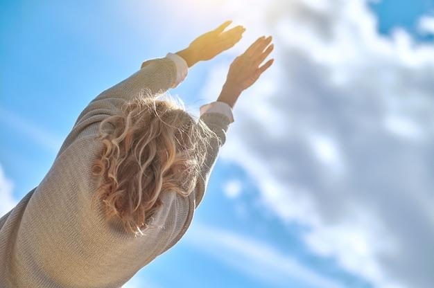 Vista de trás de uma mulher esticando as mãos em direção ao sol