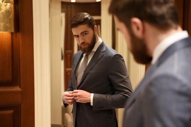 Vista de trás do homem bonito, olhando no espelho