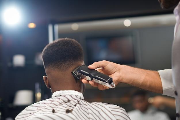 Vista de trás do processo de aparar cabelo na barbearia