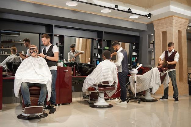 Vista de trás dos barbeiros atendendo a clientes na barbearia