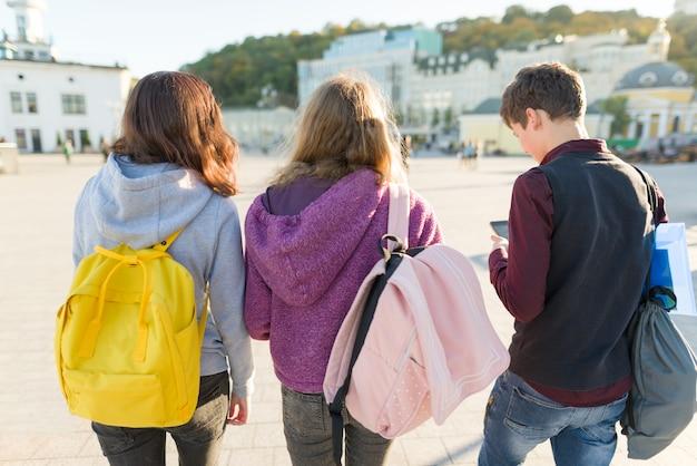Vista de trás em três estudantes do ensino médio com mochilas