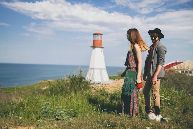 Vista de trás. jovem elegante hipster casal apaixonado, caminhando com um cachorro no campo