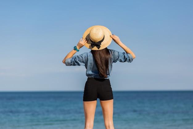 Vista de trás. mulher de chapéu de palha, com figura olhando para o mar.