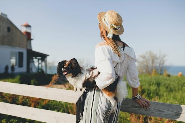 Vista de trás para a frente mulher elegante no campo, segurando um cachorro, humor positivo e feliz, verão, chapéu de palha, roupa de estilo boêmio,