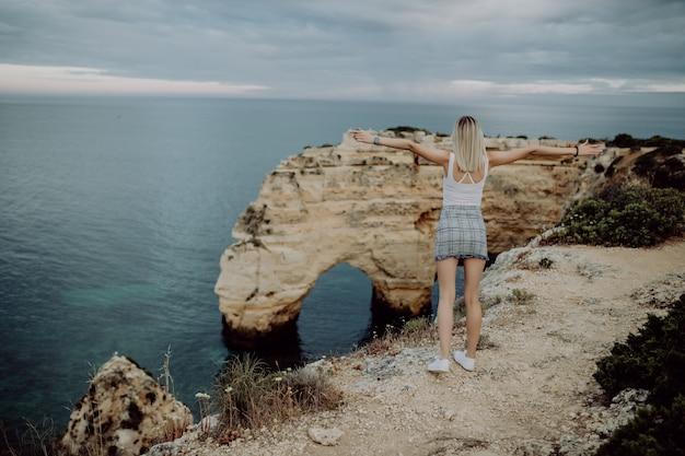 Vista de trás. uma jovem turista aprecia as belas vistas do oceano atlântico