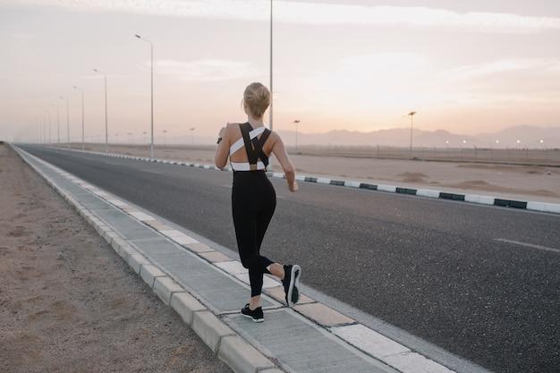 Vista de treino de volta na estrada de mulher jovem e atraente em roupas esportivas, correndo na manhã de sol. estilo de vida saudável, treinamento, forte desportista.
