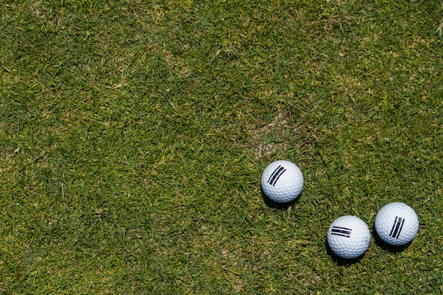 Vista de três bolas de golfe em um canto em um fundo da grama verde.